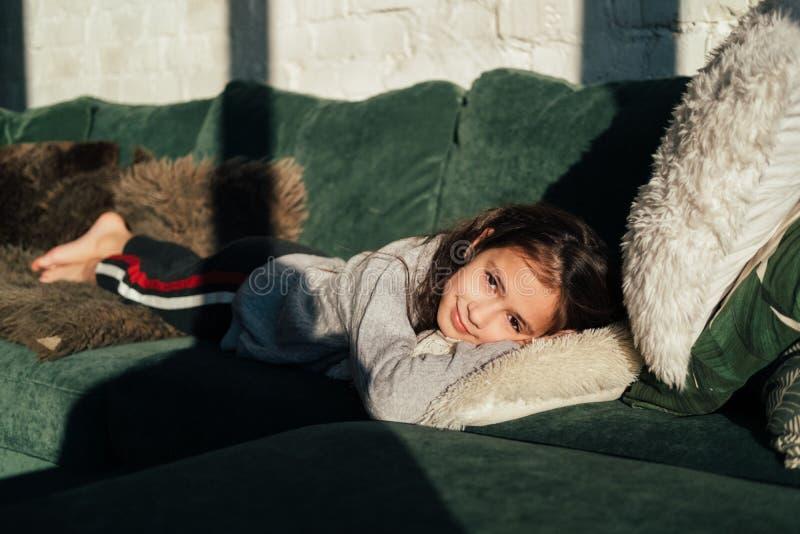 Niña linda que descansa en casa Niño hermoso joven que miente en el sofá fotos de archivo