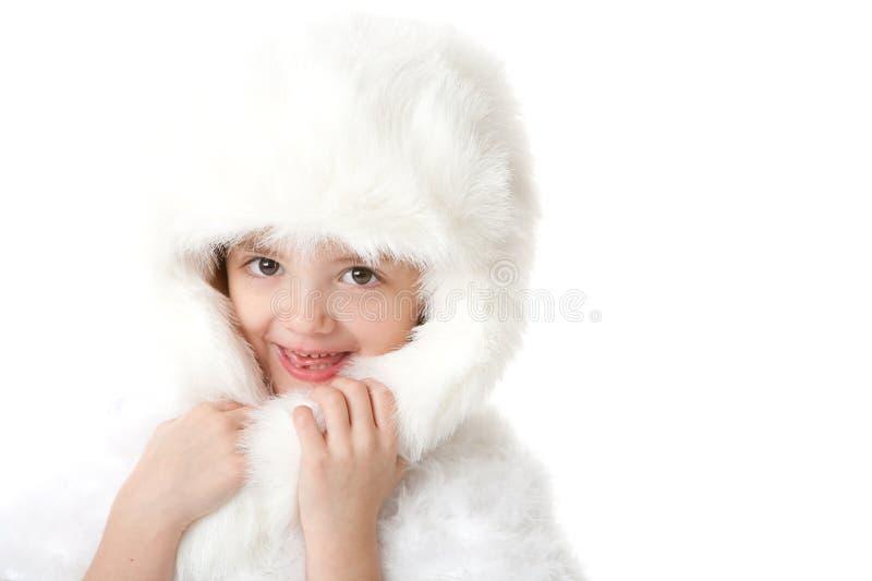 Niña linda que desgasta un abrigo de pieles y un sombrero blancos fotos de archivo libres de regalías