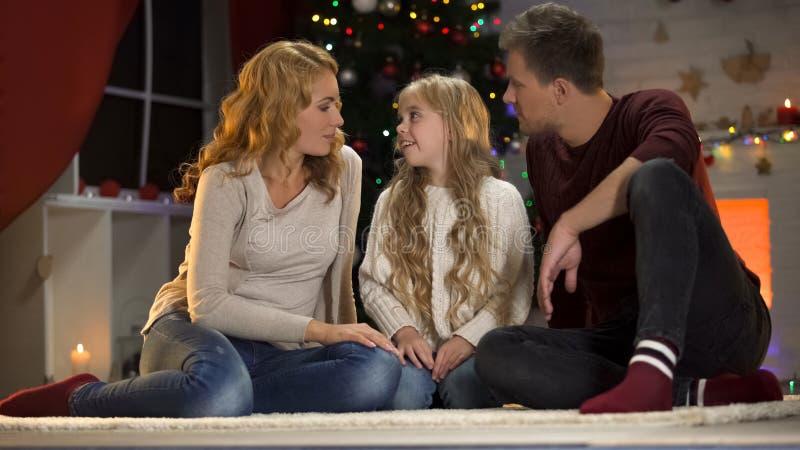 Niña linda que dice a padres el deseo de Navidad, atmósfera festiva, unidad foto de archivo