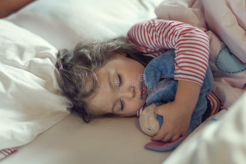 Niña linda que duerme con su juguete relleno imagen de archivo