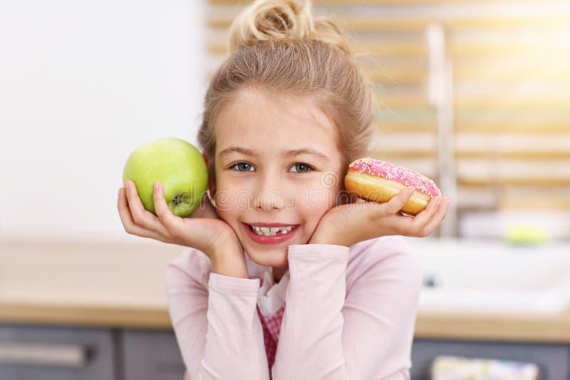 Niña linda que elige entre la manzana y el buñuelo en la cocina imagen de archivo libre de regalías