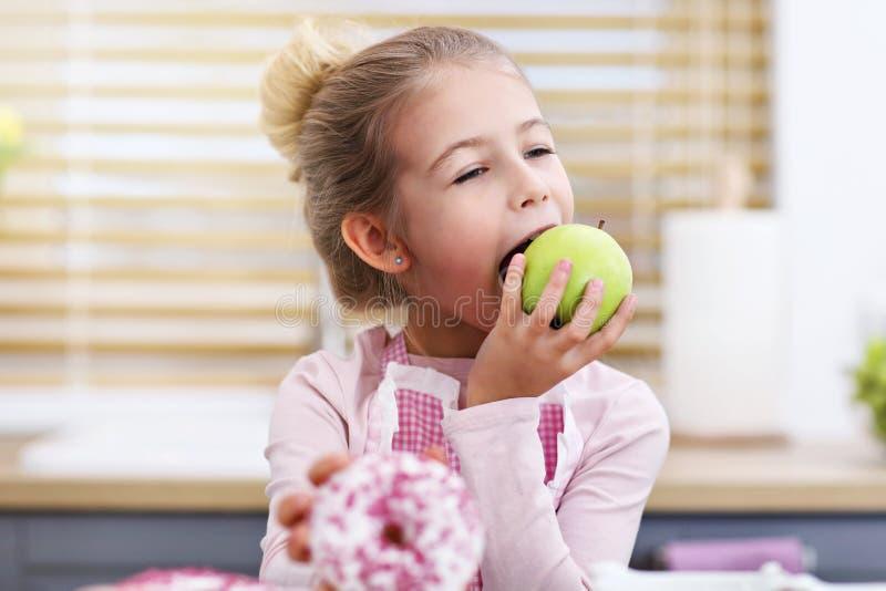 Niña linda que elige entre la manzana y el buñuelo en la cocina fotos de archivo