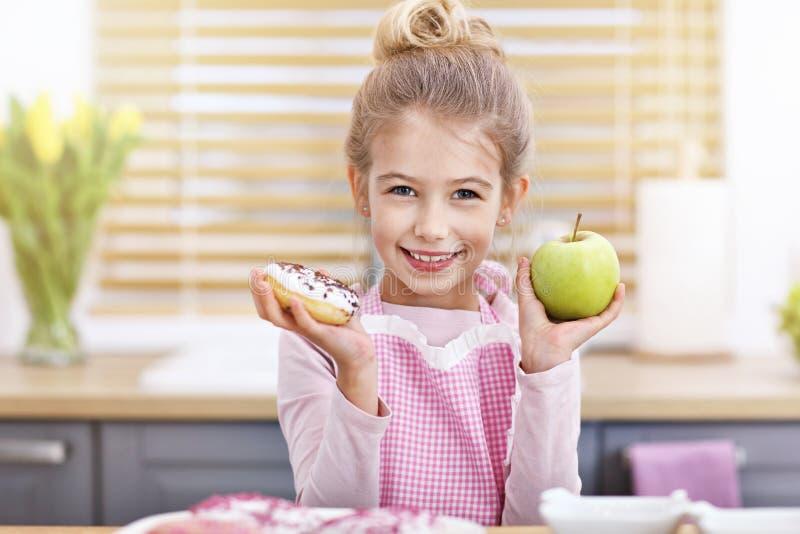 Niña linda que elige entre la manzana y el buñuelo en la cocina imagen de archivo