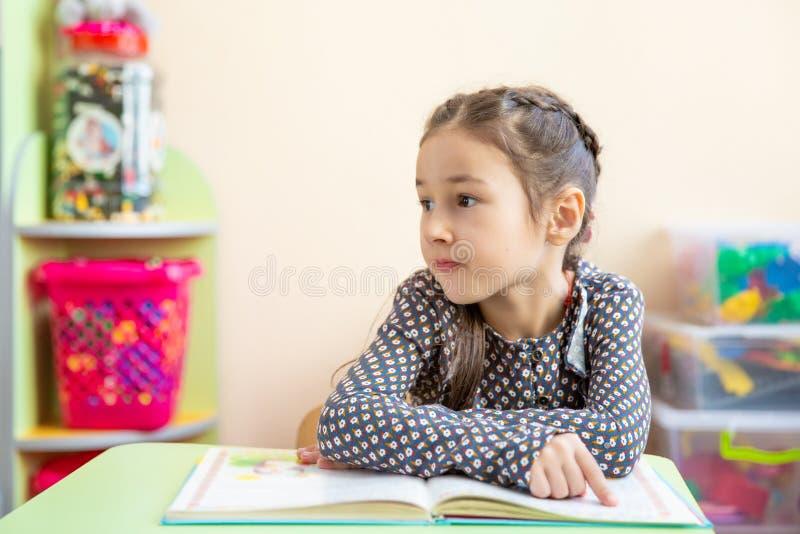Niña linda que hace la preparación, leyendo un libro, páginas que colorean, una escritura y una pintura Pintura de los niños Dren fotos de archivo libres de regalías
