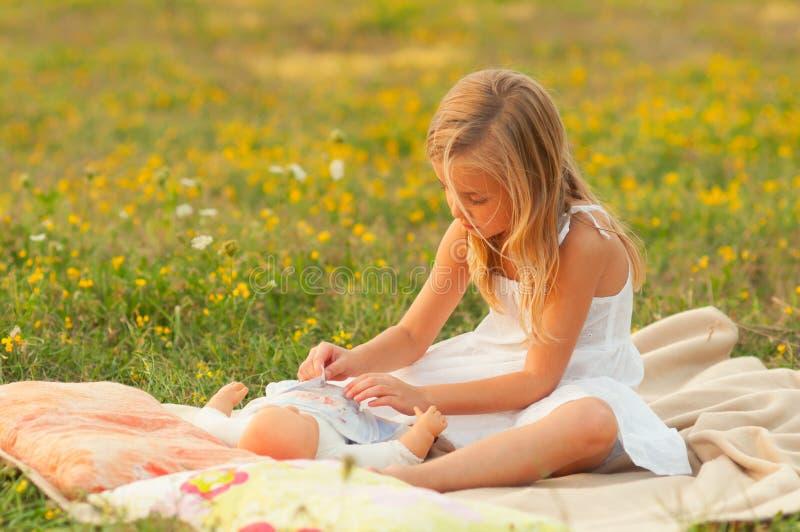 Niña linda que juega con el juguete del bebé en el prado imagenes de archivo