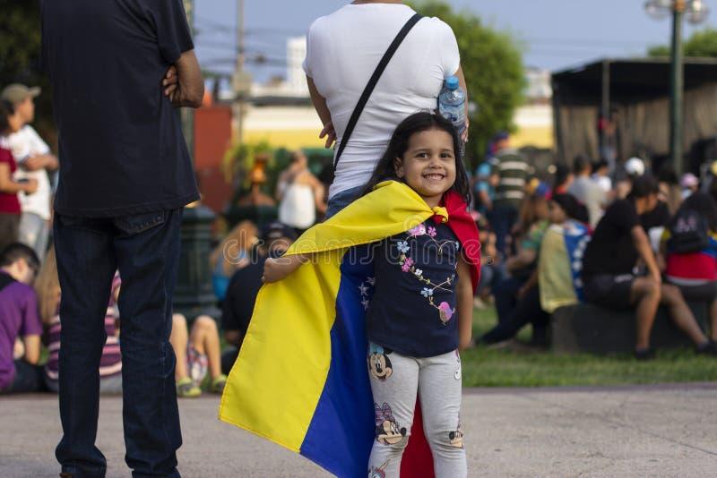 Niña linda que juega con la bandera venezolana en la protesta imagenes de archivo