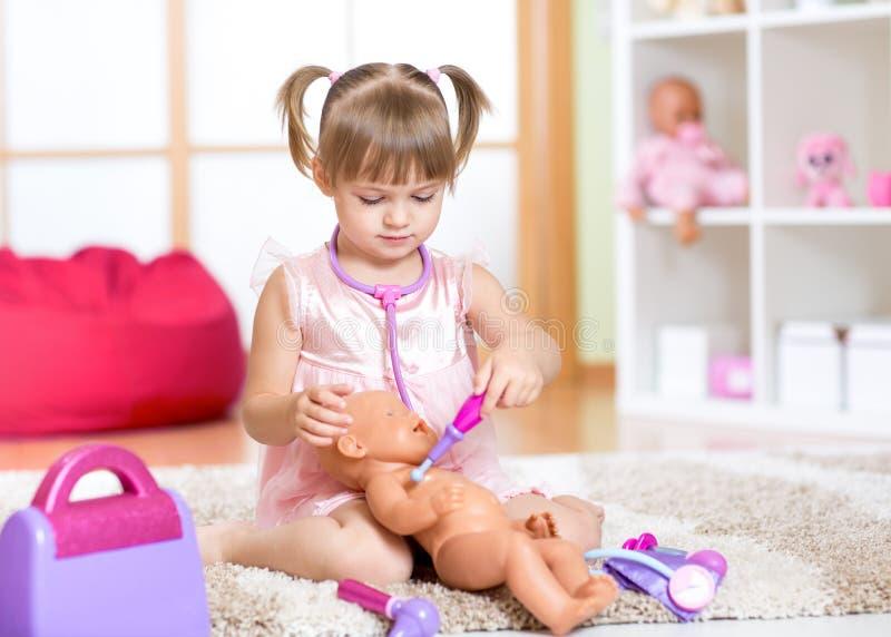Niña linda que juega con la muñeca en casa foto de archivo libre de regalías