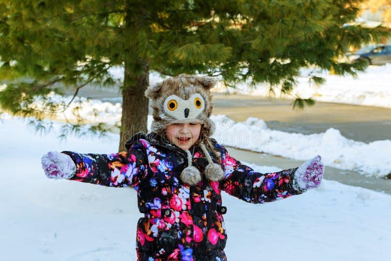 Niña linda que juega con nieve en parque del invierno imágenes de archivo libres de regalías