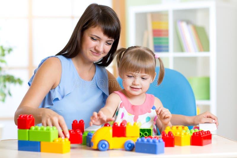 Niña linda que juega el bloque con la madre en casa imágenes de archivo libres de regalías