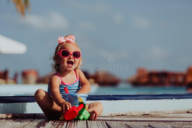 Niña linda que juega en piscina en la playa foto de archivo