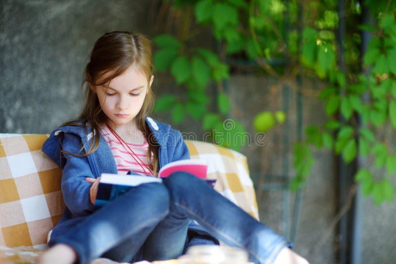 Niña linda que lee un libro al aire libre foto de archivo