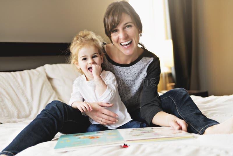 Niña linda que lee un libro con su madre en el dormitorio fotos de archivo