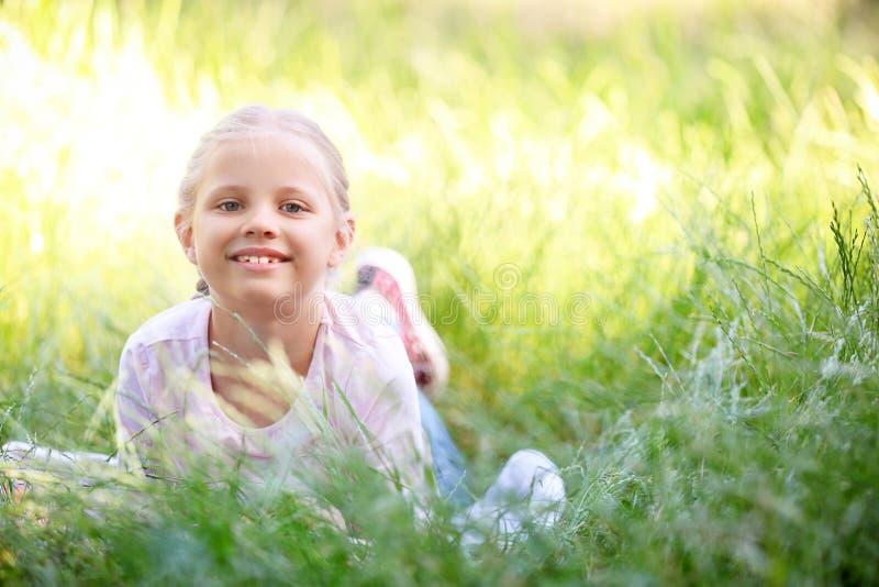 Niña linda que miente en hierba verde al aire libre imagenes de archivo