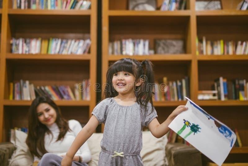 Niña linda que pinta una imagen con la madre y mostrar su trabajo en casa imagen de archivo libre de regalías