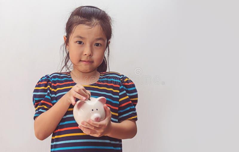 Niña linda que pone la moneda en la hucha imagen de archivo libre de regalías