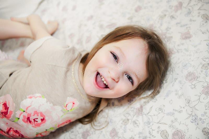 Niña linda que ríe en cama imagen de archivo