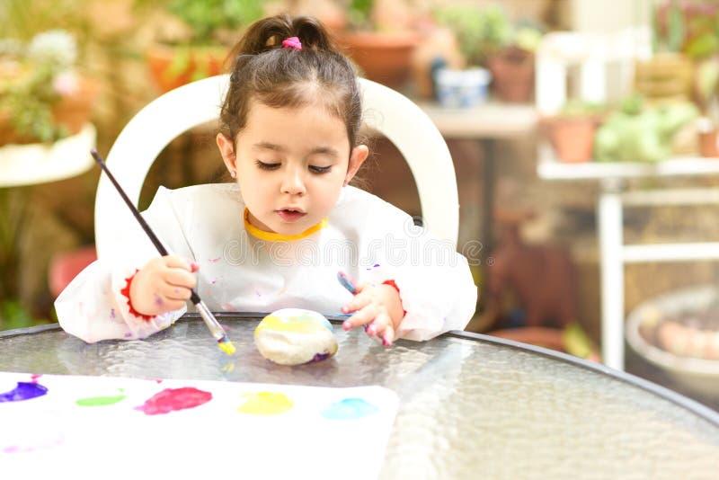 Niña linda que se divierte, coloreando con el cepillo, jugar y la pintura Preescolar con la pintura en el jardín fotos de archivo