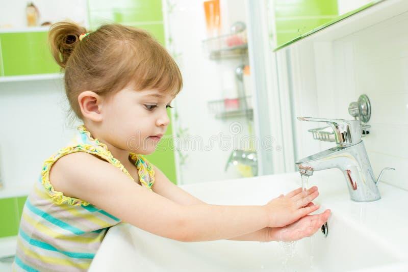 Niña linda que se lava las manos en cuarto de baño fotos de archivo libres de regalías