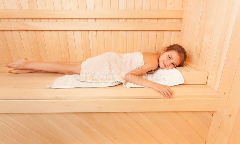 Niña linda que se relaja en banco en la sauna fotografía de archivo libre de regalías