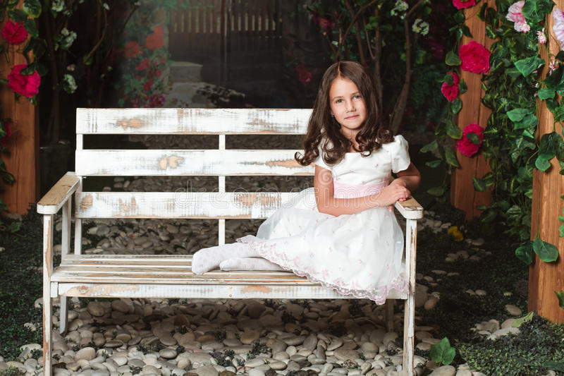 Niña linda que se sienta en el jardín florecido imagen de archivo libre de regalías