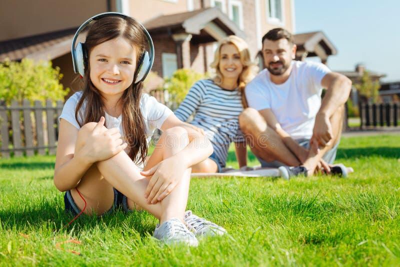Niña linda que se sienta en hierba y música que escucha imágenes de archivo libres de regalías