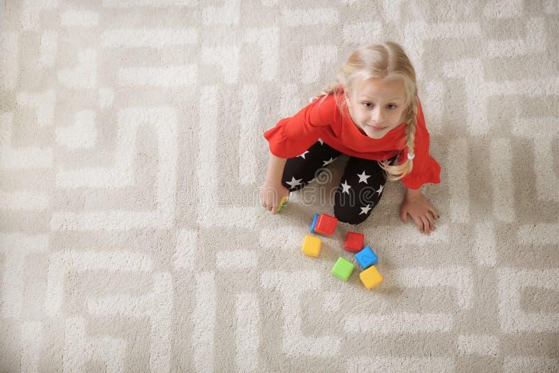 Niña linda que se sienta en la alfombra acogedora con los cubos imagen de archivo