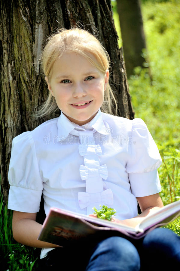 Niña linda que se sienta en la hierba cerca de un árbol fotografía de archivo libre de regalías