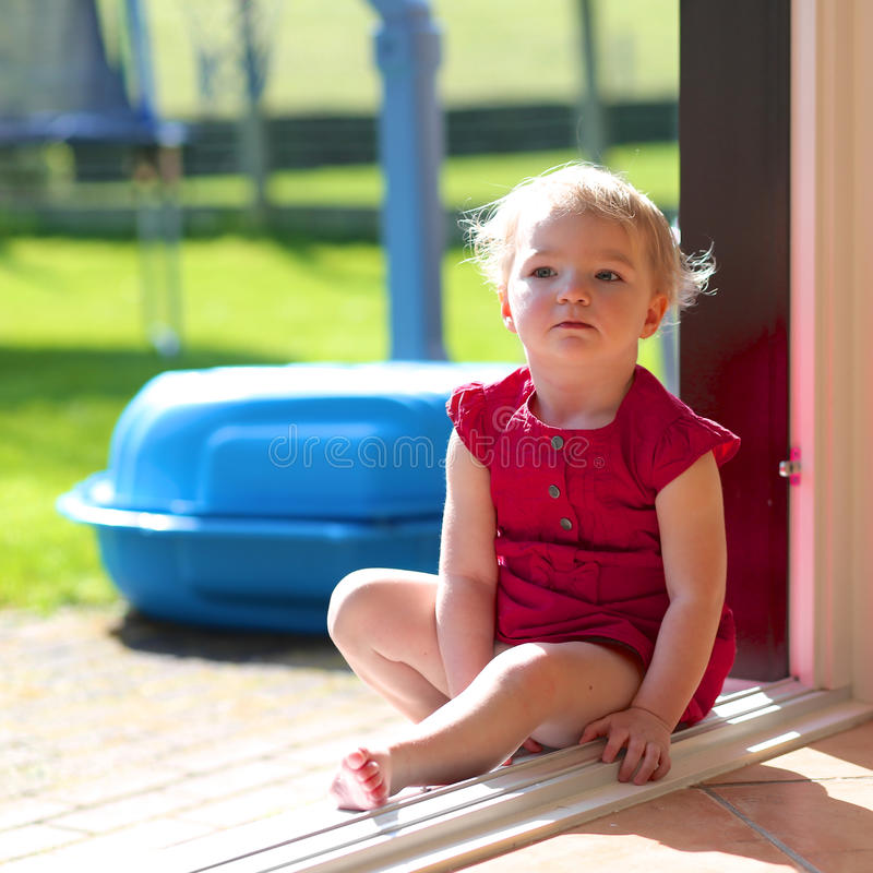 Niña linda que se sienta en la puerta deslizante abierta foto de archivo