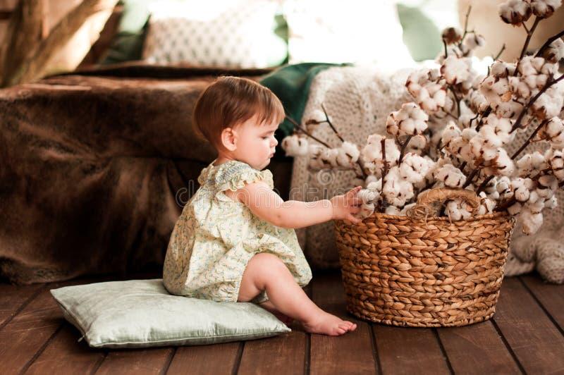 Niña linda que se sienta en las almohadas cerca de cesta de mimbre con las flores del algodón imagen de archivo