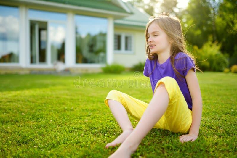 Niña linda que se sienta en una hierba en el patio trasero imagen de archivo