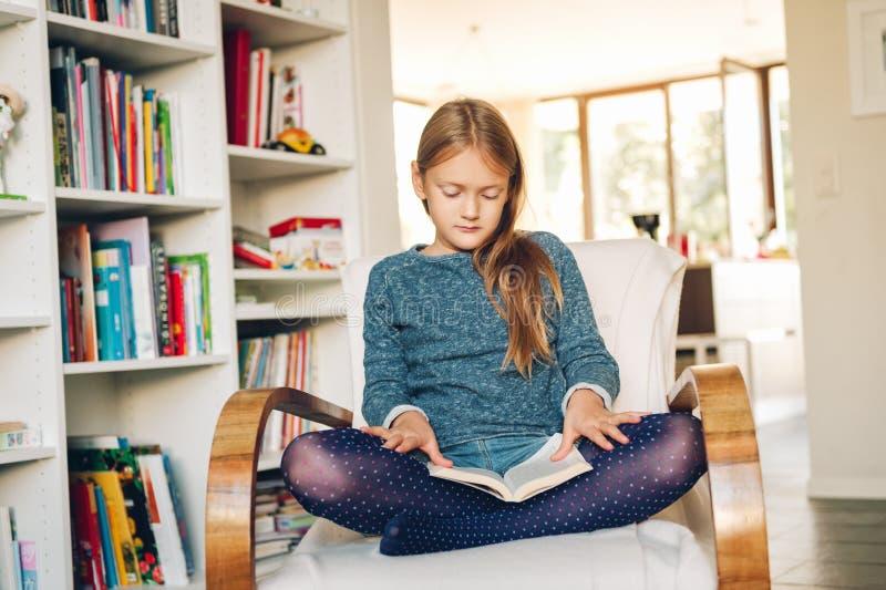 Niña linda que se sienta en una silla en casa y que lee un libro imagenes de archivo