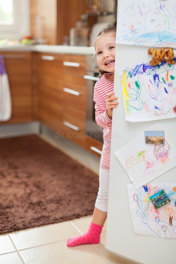 Niña linda que sonríe detrás de puerta del refrigerador en cocina foto de archivo