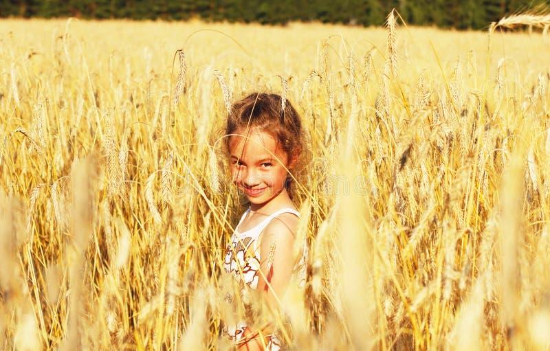 Niña linda que sonríe en un campo de trigo en la puesta del sol imagen de archivo