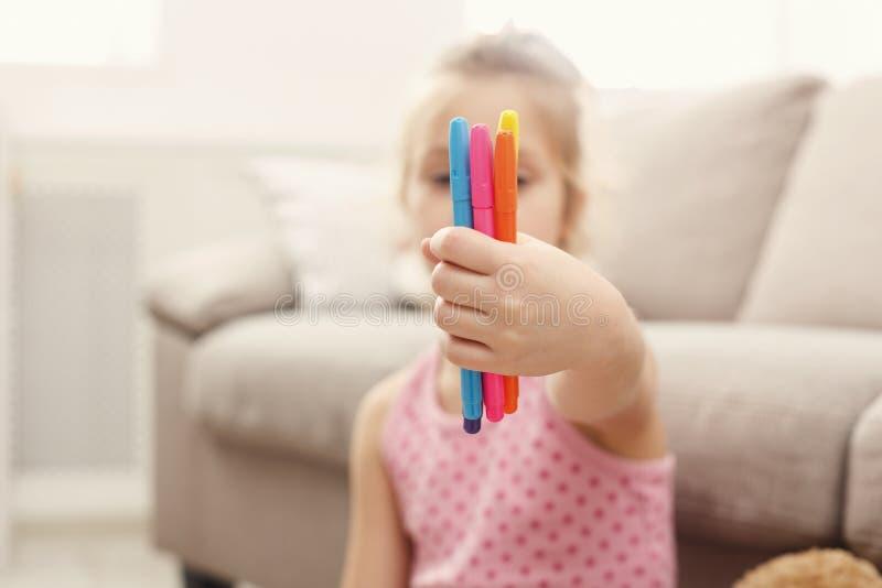 Niña linda que sostiene las plumas coloridas del fieltro, espacio de la copia fotografía de archivo libre de regalías