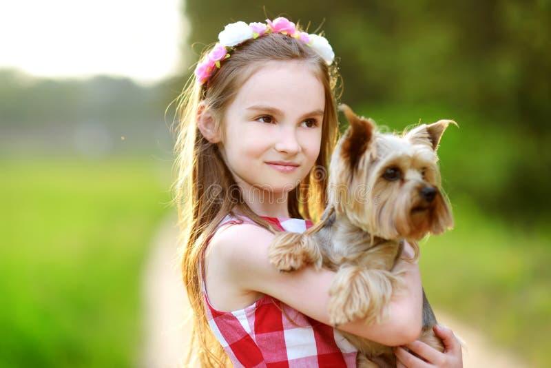 Niña linda que sostiene su perro del terrier de Yorkshire foto de archivo
