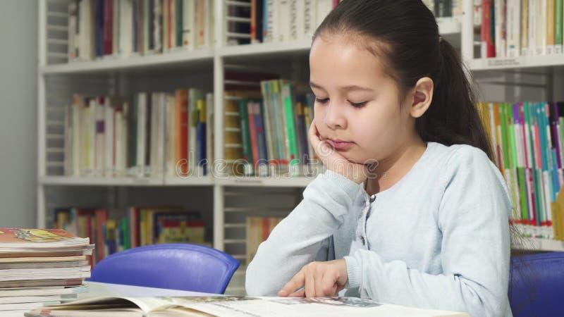 Niña linda que sueña mientras que lee un libro en la biblioteca foto de archivo