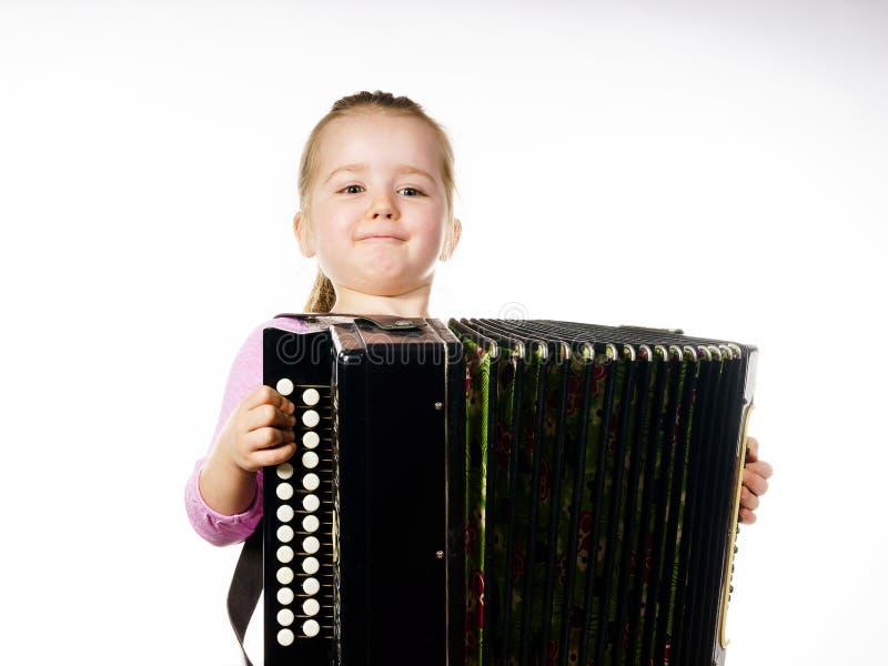 Niña linda que toca la armónica, concepto de la educación de la música fotografía de archivo libre de regalías