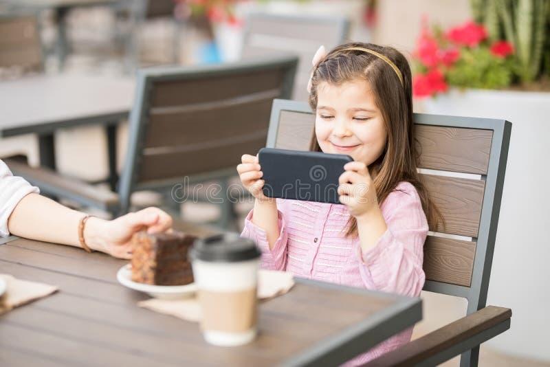 Niña linda que usa el teléfono elegante en el café foto de archivo