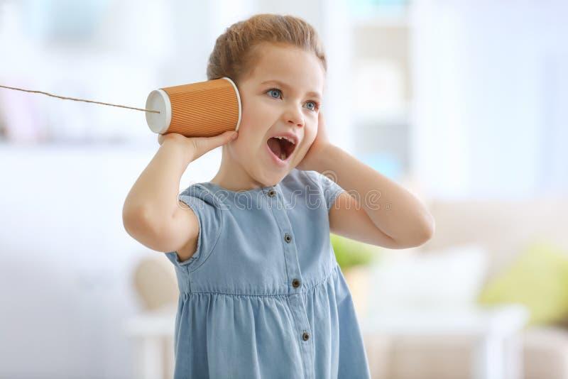 Niña linda que usa la taza plástica como teléfono mientras que juega en casa imagenes de archivo