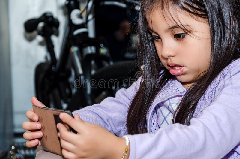Niña linda que usa un smartphone moderno fotografía de archivo
