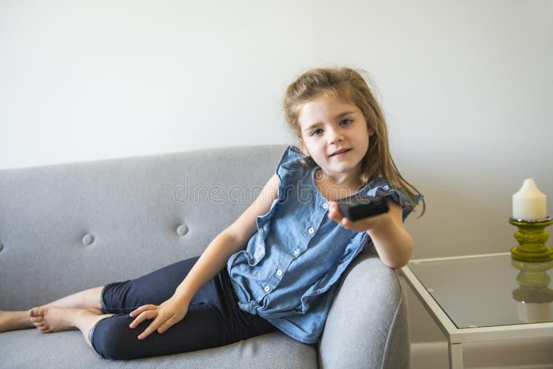 Niña linda que ve la TV en el sofá en el sofá imagen de archivo libre de regalías