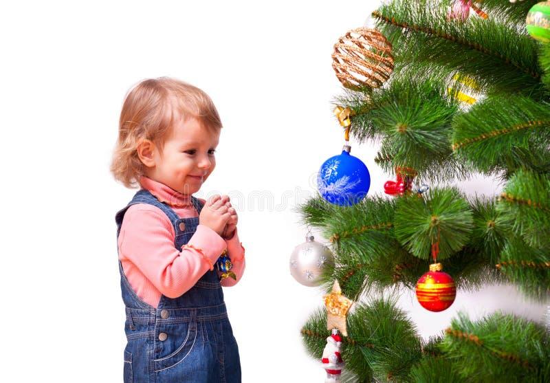 Niña linda que viste el árbol de navidad foto de archivo