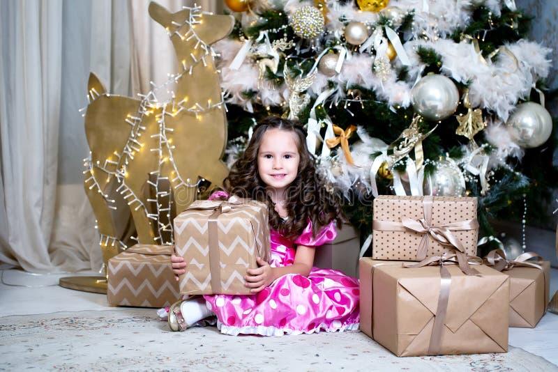 Niña linda sonriente cerca de los regalos y del árbol de navidad cercanos A?o Nuevo o celebraci?n de la Navidad en casa imagen de archivo