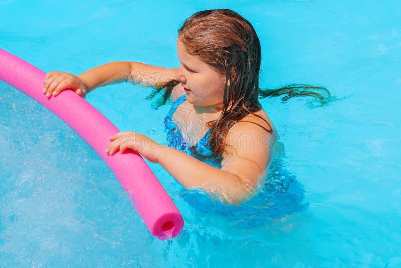 Niña linda sonriente en piscina en día soleado foto de archivo