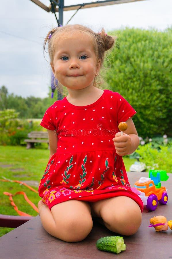 Niña linda sonriente en vestido rojo fotos de archivo