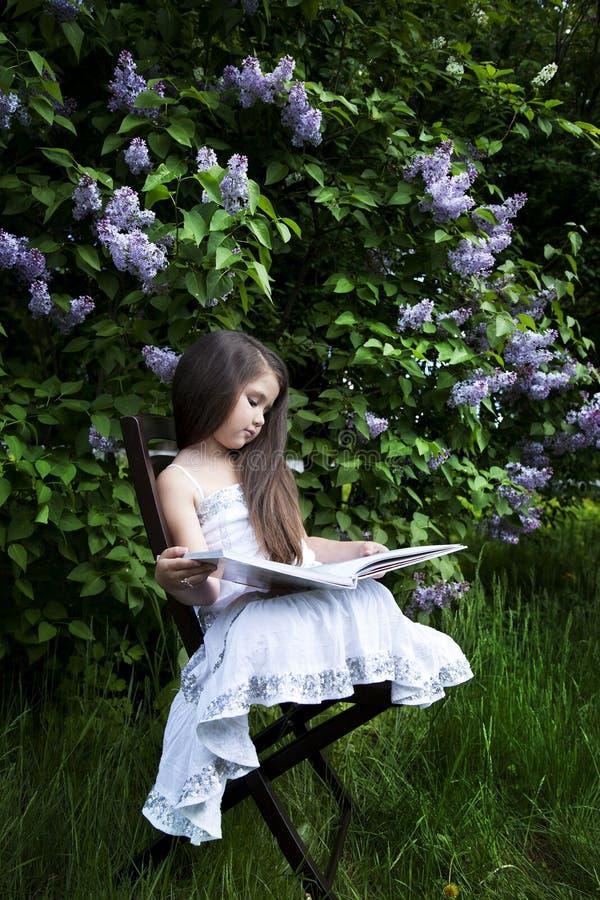Niña linda, vestida en un vestido blanco, sentándose en el jardín en el parque y leyendo un libro lilas verdes y florecientes foto de archivo