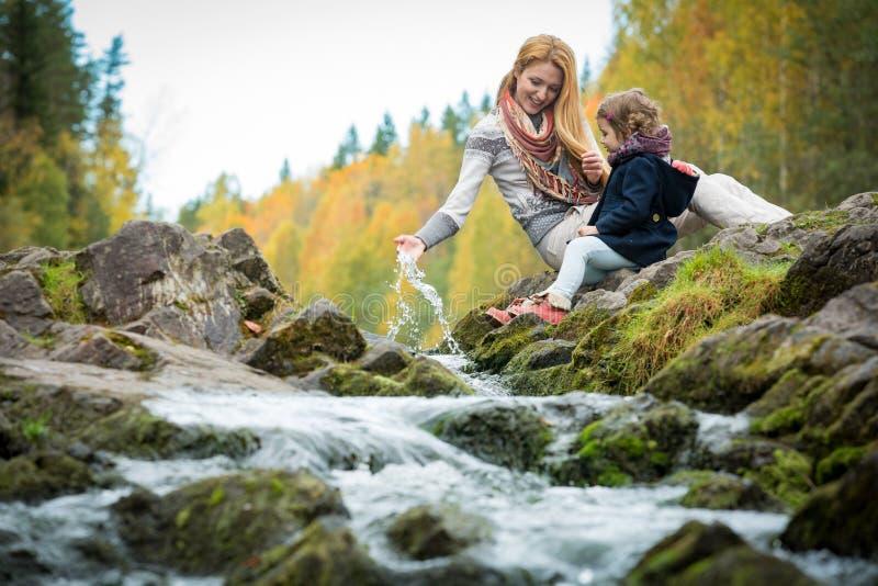 Niña linda y madre que se sientan en una roca en bosque del otoño en la corriente fotos de archivo