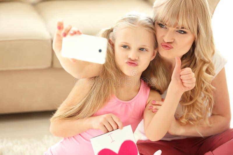 Niña linda y su madre que toman el selfie con la tarjeta hecha a mano en casa imagenes de archivo