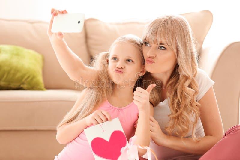 Niña linda y su madre que toman el selfie con la tarjeta hecha a mano en casa imagen de archivo libre de regalías
