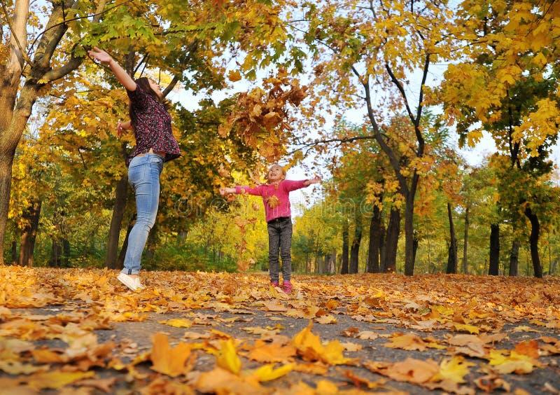 Niña linda y sus juegos de la madre con las hojas de un otoño fotos de archivo